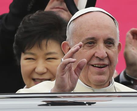 Pope Francis waves upon his arrival at Seoul Air Base, as South Korean President Park Geun-hye (L) smiles, in Seongnam, August 14, 2014. REUTERS/Ahn Young-joon/Pool