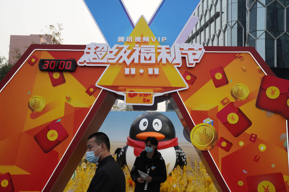 Workers wearing masks stand near a promotional booth for Tencent video in Beijing on Nov. 11, 2020. China's market regulator on Monday, Dec. 14, 2020 said it fined Alibaba Group and a Tencent Holdings-backed company for failing to seek approval before proceeding with some acquisitions. It also is launching a review of a merger of two online streaming platforms in the latest tightening of controls over the internet sector. (AP Photo/Ng Han Guan)