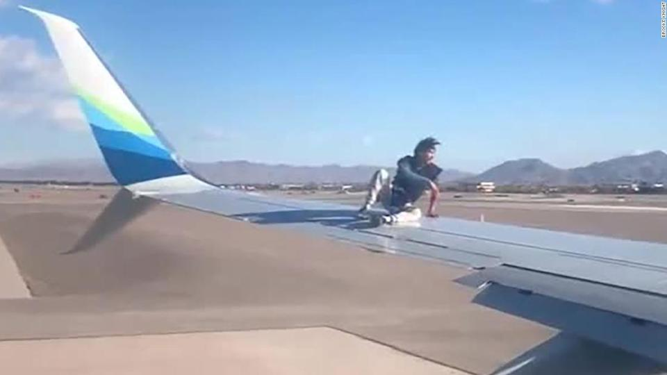 """<p>A man sits on the wing of an Alaska Airlines plane minutes before takeoff at McCarran International Airport in Las Vegas, Nevada.</p><div class=""""cnn--image__credit""""><em><small>Credit: Brooke Knight / Brooke Knight</small></em></div>"""