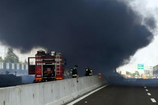 Firefighters work at the scene where a tanker truck exploded on a motorway just outside Bologna, northern Italy, on August 6, 2018
