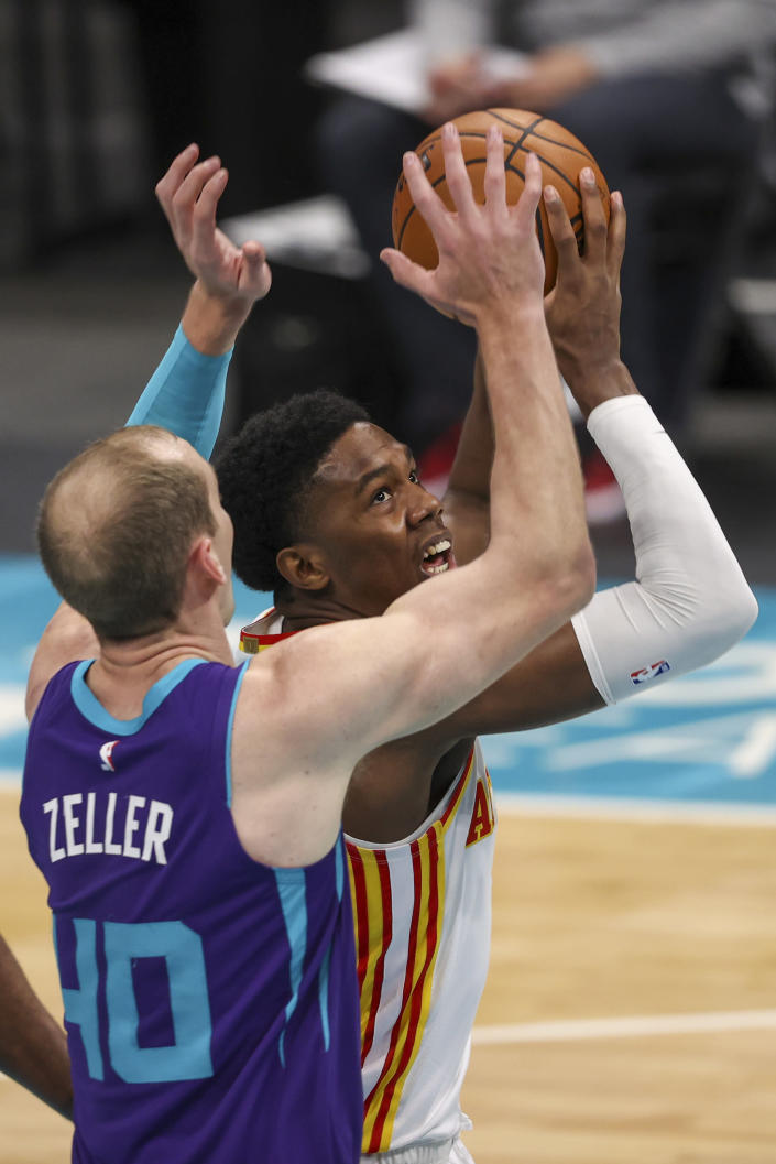 Atlanta Hawks forward Nathan Knight, right, shoots against Charlotte Hornets center Cody Zeller (40) during the second quarter of an NBA basketball game in Charlotte, N.C., Sunday, April 11, 2021. (AP Photo/Nell Redmond)