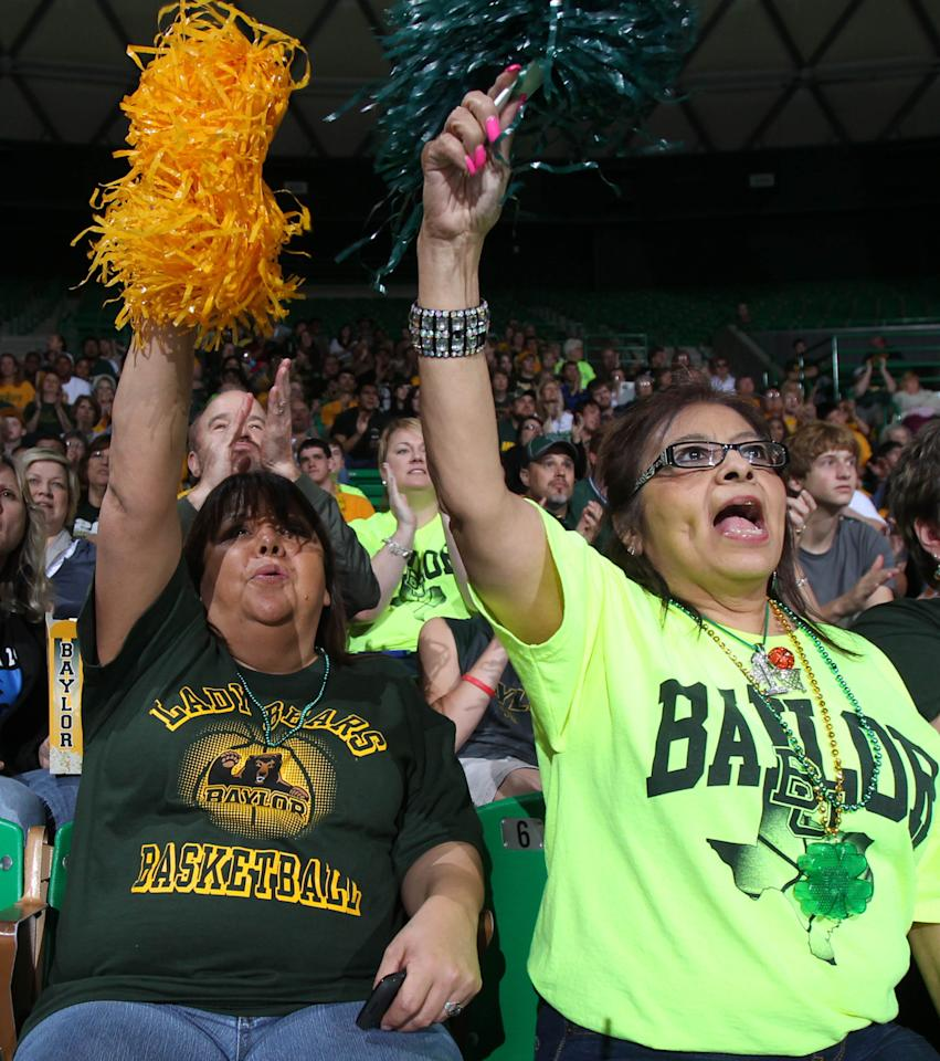 Baylor fans Dee Dee Gonzales, left, and Bertha Arellano watch large video monitors in Waco, Texas, as Baylor takes on Notre Dame in the NCAA women's college basketball tournament Final Four championship game in Denver, Tuesday, April 3, 2012. Hundreds of fans gathered inside the Ferrell Center to watch the game. (AP Photo/Waco Tribune-Herald, Duane A. Laverty)