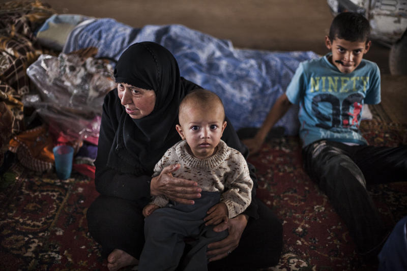 A displaced Syrian woman and her grandson in a refugee camp In the border with Turkey, near Azaz village, Syria, Sunday, Sept. 30, 2012. (AP Photo/ Manu Brabo)