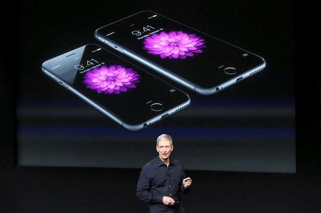 FILE PHOTO: Apple CEO Tim Cook stands in front of a screen displaying the IPhone 6 during a presentation at Apple headquarters in Cupertino