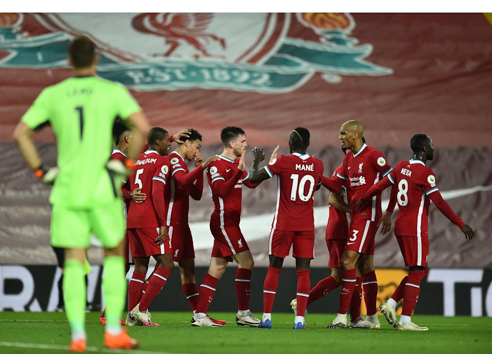 Liverpool players celebrate the go-ahead goal by Andy Robertson (middle) as Arsenal keeper Bernd Leno looks on. (Andrew Powell/Getty Images)