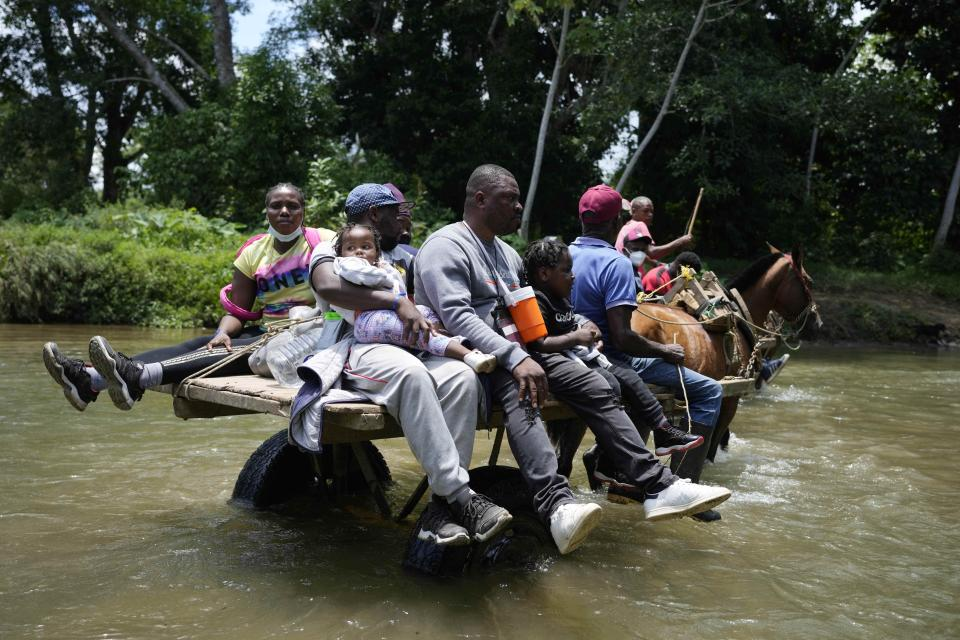 Migrants cross the Acandi River on a horse cart in Acandi, Colombia, Tuesday, Sept. 14, 2021. The migrants, following a well-beaten, multi-nation journey towards the U.S., will continue their journey through the jungle known as the Darien Gap. (AP Photo/Fernando Vergara)