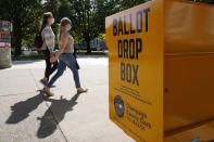 FILE - In this Oct. 6, 2020, file photo, University of Illinois students walk past a mail-in ballot drop box that sits on the northwest corner of the university's Quad in Urbana, Ill. As it has for more than 170 years, The Associated Press will count the vote and report the results of presidential, congressional and state elections quickly, accurately and without fear or favor on Nov. 3 and beyond. (AP Photo/Charles Rex Arbogast, File)