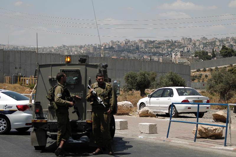 Israeli soldiers stand guard at a checkpoint between Jerusalem and the West Bank city of Bethlehem on June 29, 2015 (AFP Photo/Ahmad Gharabli)