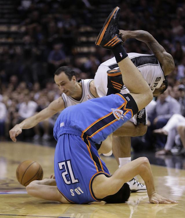 Oklahoma City Thunder's Steven Adams (12) flips over as he vies against San Antonio Spurs' Manu Ginobili, back left, and Kawhi Leonard, back right, for a loose ball during the second half of Game 5 of the Western Conference finals NBA basketball playoff series, Thursday, May 29, 2014, in San Antonio. (AP Photo/Eric Gay)