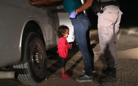 A two-year-old Honduran asylum seeker cries as her mother is searched and detained near the U.S.-Mexico border on June 12, 2018 - Credit: John Moore/Getty Images