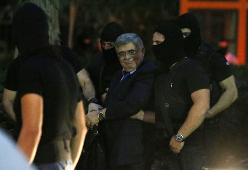 Leader of the extreme far-right Golden Dawn party, Nikos Michaloliakos, center, smiles toward his supporters as he escorted by anti-terror police upon his arrival to a court for a preliminary hearing into charges of participating in a criminal organization in Athens, Wednesday, Oct. 2, 2013. Three lawmakers from Greece's extremist right-wing Golden Dawn party were released from custody Wednesday pending trial, after they provided initial testimony in criminal investigation triggered by the slaying of a left-wing rapper. A fourth lawmaker, Ioannis Lagos, was jailed pending trial. (AP Photo/Thanassis Stavrakis)