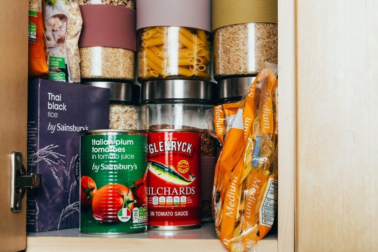 Cupboard containing tinned food and rice, dried pasta