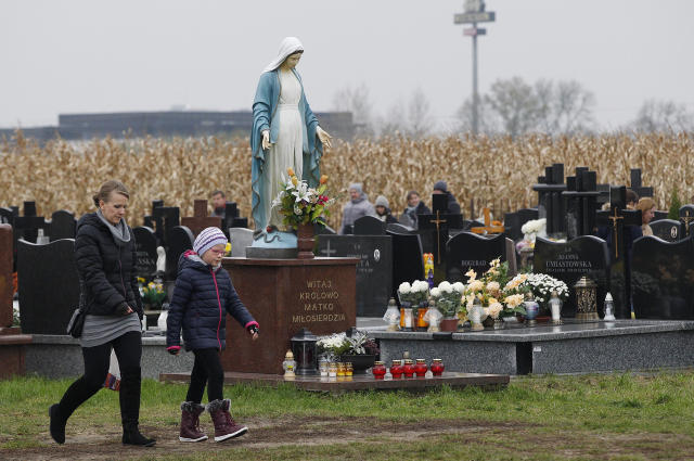 <p>People visit a cemetery in Lomna near Warsaw, Poland, Wednesday, Nov. 1, 2017. Candles and flowers cover tombstones in graveyards across Poland on All Saints' Day. (Photo: Czarek Sokolowski/AP) </p>