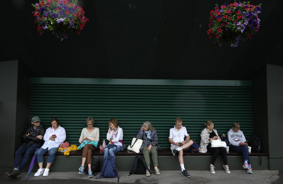 Spectators take shelter outside Court no. 2 during a rain delay on day one of the Wimbledon Tennis Championships in London, Monday June 28, 2021. (AP Photo/Kirsty Wigglesworth)