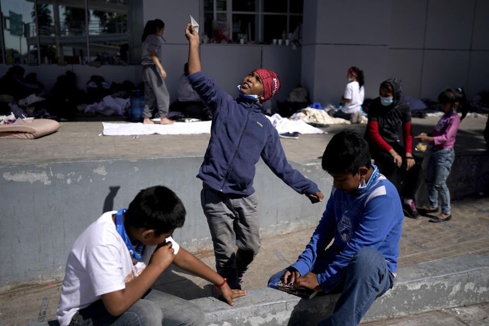 A migrant boy, center, launches a paper airplane while playing with other migrant children at a plaza near the McAllen-Hidalgo International Bridge point of entry into the U.S., after being caught trying to cross into the U.S. and deported, Thursday, March 18, 2021, in Reynosa, Mexico. (AP Photo/Julio Cortez)