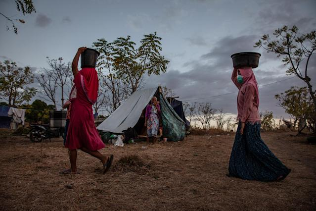 <p>Villagers carry buckets of water at a temporary shelter in Kayangan on Aug. 11, 2018 in Lombok Island, Indonesia. (Photo: Ulet Ifansasti/Getty Images) </p>