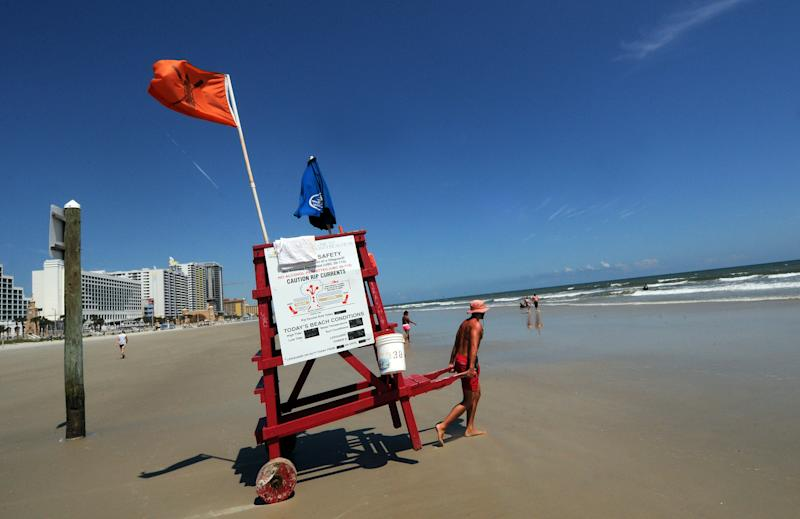 A lifeguard moves his chair on a calm and quiet beach in Titusville, Fla., several days ahead of the Hurricane Dorian which is expected to become a Category 4 hurricane before making landfall in Florida on Labor Day. (Photo: Paul Hennessy/SOPA Images via ZUMA Wire)