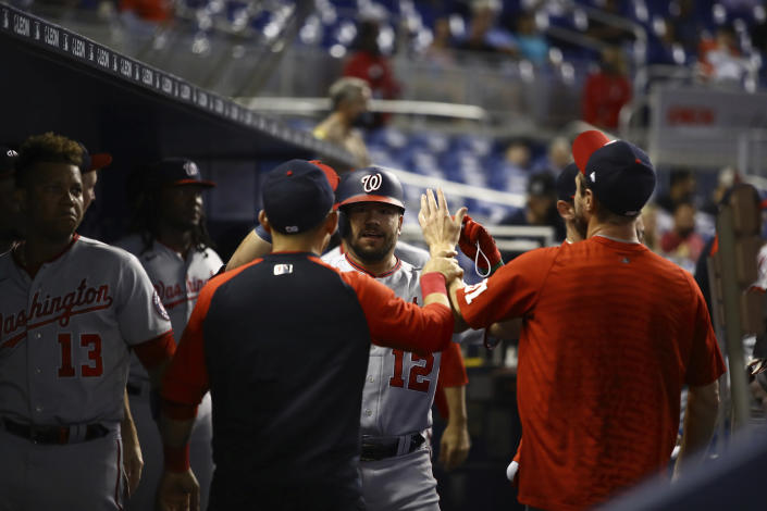 Washington Nationals left fielder Kyle Schwarber (12) celebrates a solo home run with teammates in the dugout during the first inning of a baseball game on Thursday, June 24, 2021, in Miami. (AP Photo/Mary Holt)