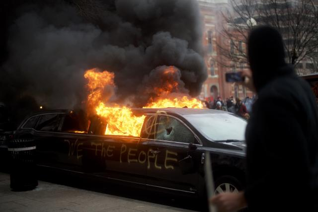 """A limousine with the graffiti of """"We the People"""" spray-painted on the side is set ablaze. (Mark Makela/Getty Images)"""