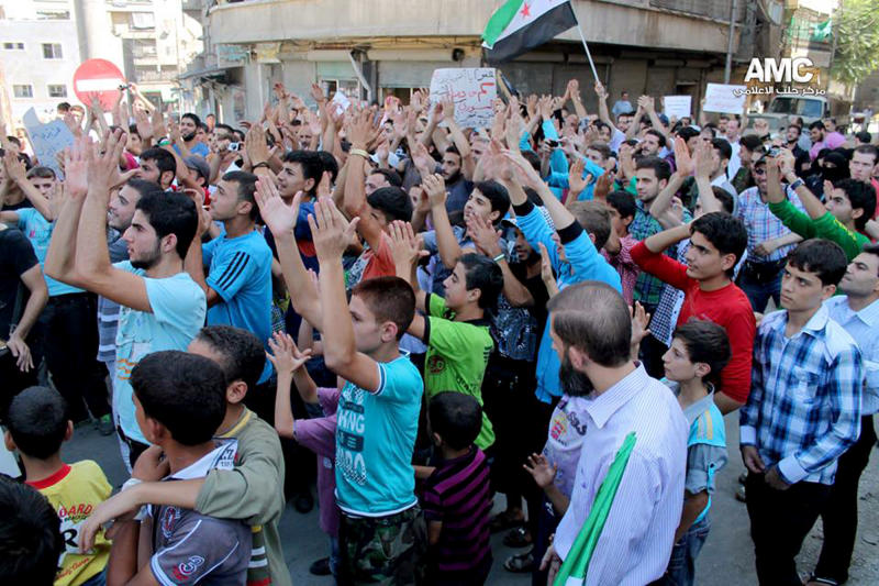 This citizen journalism image provided by Aleppo Media Center AMC which has been authenticated based on its contents and other AP reporting, shows anti-Syrian regime protesters chanting slogans during a demonstration in Aleppo, Syria, Friday, Sept. 20, 2013. Syria's main Western-backed opposition group on Friday slammed al-Qaida-linked gunmen and their expanding influence in the country, saying the jihadis' push to establish an Islamic state undermines the rebels' struggle for a free Syria. (AP Photo/Aleppo Media Center, AMC)