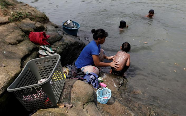 Ratna, a local, bathes her son as she washes clothes in the river - REUTERS