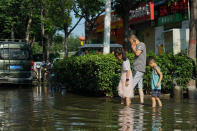 People walk along a flooded street in Xinxiang in central China's Henan Province, Monday, July 26, 2021. Forecasters Monday said more heavy rain is expected in central China's flood-ravaged Henan province, where the death toll continues to rise after flash floods last week that killed dozens of people. (AP Photo/Dake Kang)