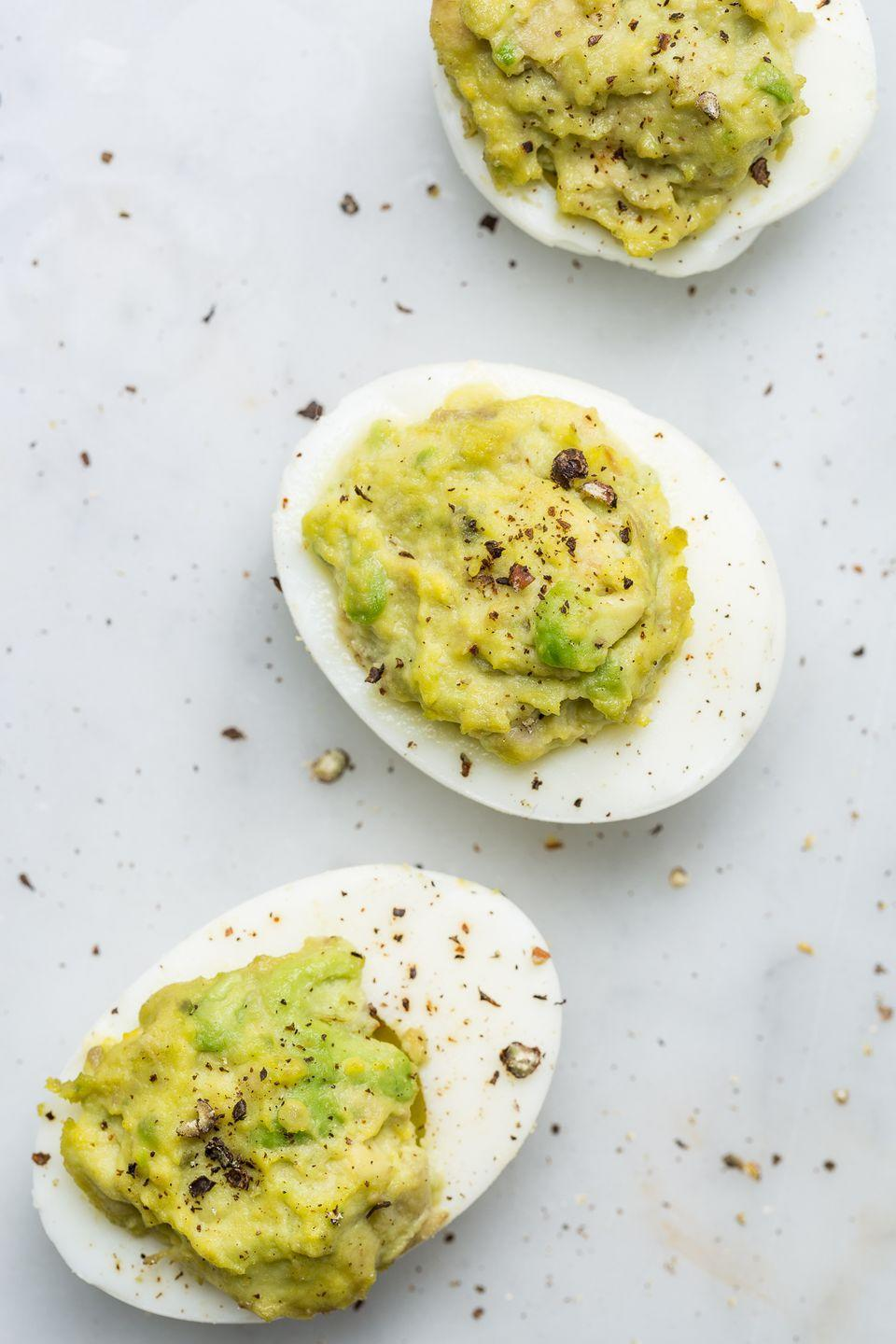 """<p>These guac deviled eggs are the perfect finger food.</p><p>Get the recipe from <a href=""""https://www.delish.com/holiday-recipes/easter/recipes/a58648/best-guacamole-deviled-eggs-recipe/"""" rel=""""nofollow noopener"""" target=""""_blank"""" data-ylk=""""slk:Delish"""" class=""""link rapid-noclick-resp"""">Delish</a>.</p>"""