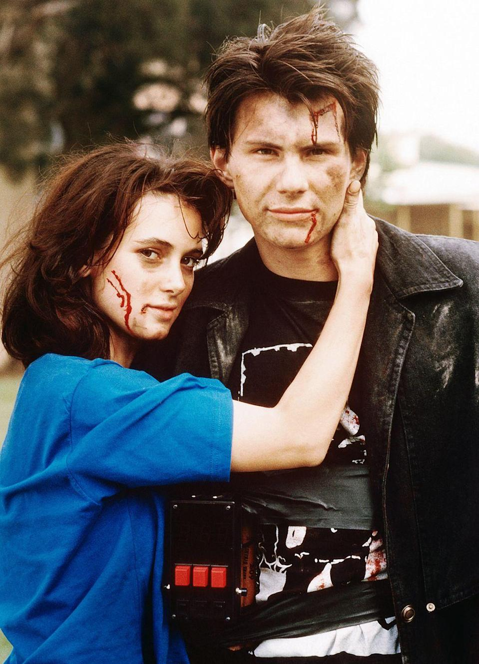 <p>Winona Ryder stars as the whip-smart Veronica Sawyer, a popular girl who hates her best friends (a trio of queen bees, all named Heather). Her life spins out of control when she falls for the new kid at school—the trench coat-wearing, gun-toting J.D., played by Christian Slater—who convinces her to kill off her clique</p>