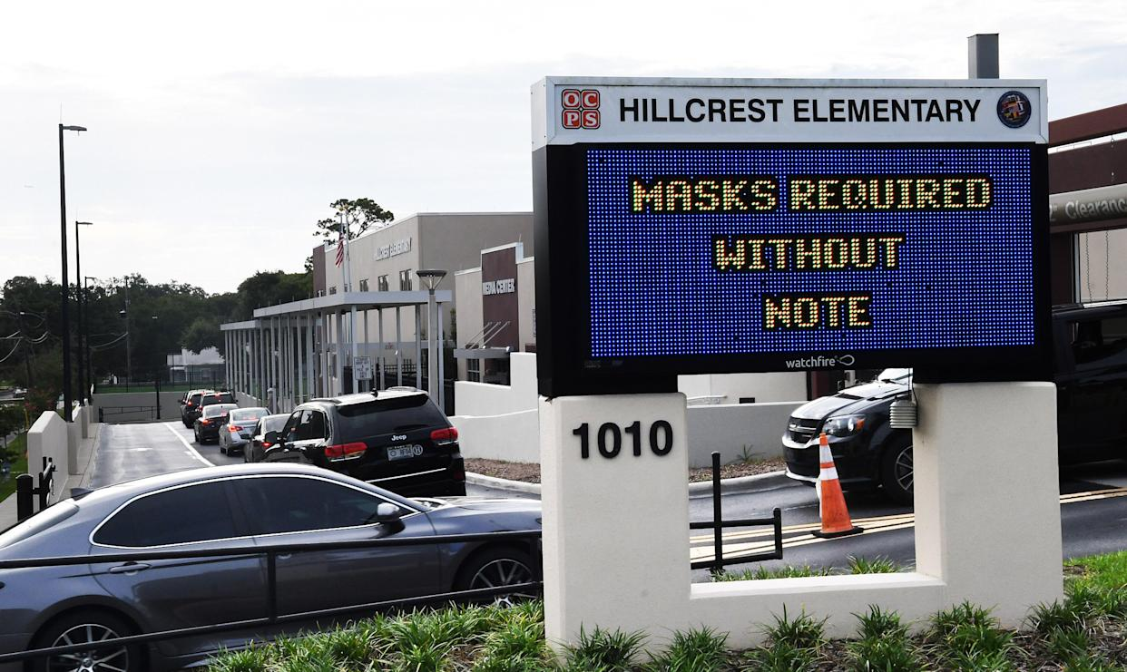 A sign outside Hillcrest Elementary School in Orlando, Fla., advises that students are required to wear face masks unless the parents opt out of the mandate by writing a note to school officials.