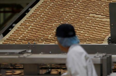 FILE PHOTO - A worker inspects biscuits on the production line of Pladis' McVities factory in London