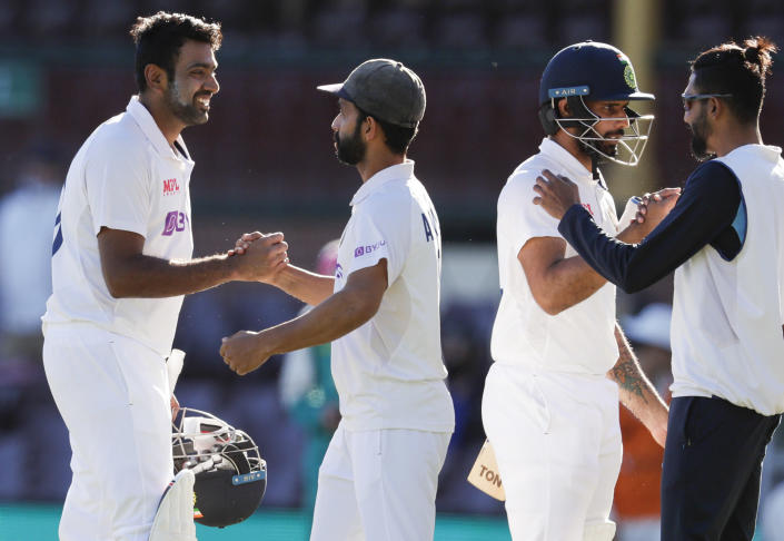 India's Ravichandran Ashwin, left, is congratulated by his captain Ajinkya Rahane as Hanuma Vihari is congratulated by teammate Mohammed Siraj, right, following play on the final day of the third cricket test between India and Australia at the Sydney Cricket Ground, Sydney, Australia, Monday, Jan. 11, 2021. The test ended in a draw and the series is at 1-1 all with one test to play. (AP Photo/Rick Rycroft)