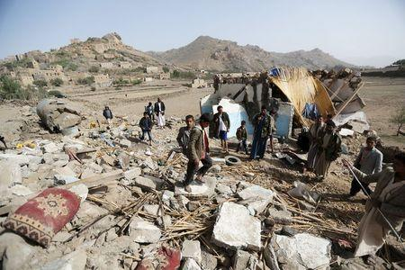 People gather around the wreckage of a house destroyed by an air strike in the Bait Rejal village, west of Yemen's capital Sanaa April 7, 2015. REUTERS/Khaled Abdullah