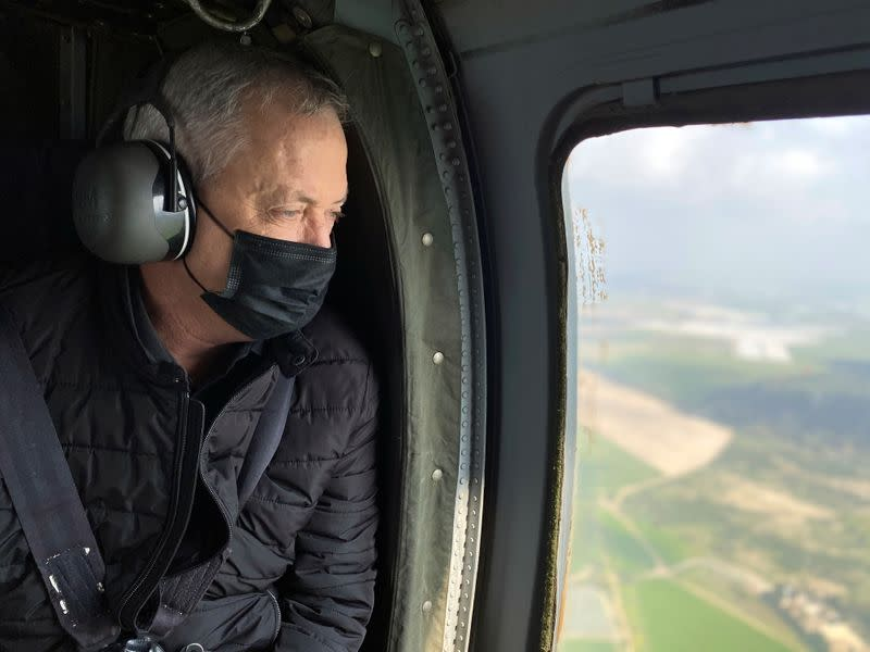 Israeli Defence Minister Benny Gantz wears a face mask as he looks out from the window of a helicopter during a tour of the Gaza border area, southern Israel