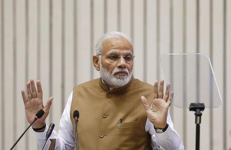 FILE PHOTO: India's Prime Minister Narendra Modi gestures as he addresses the gathering during the 'Global Mobility Summit' in New Delhi