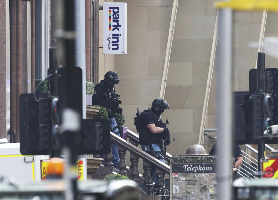 Armed police at the scene of an incident in Glasgow, Scotland, Friday June 26, 2020. Scottish police say the individual shot by armed police during an incident in Glasgow has died and that six other people including a police officer are in hospital being treated for their injuries.  (Andrew Milligan/PA via AP)