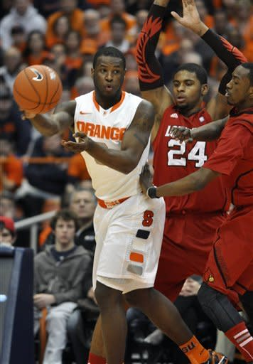 Syracuse's Dion Waiters, left, pass under pressure from Louisville's Russ Smith, right, and Chane Behannan during the first half of an NCAA college basketball game in Syracuse, N.Y., Saturday, March 3, 2012. (AP Photo/Kevin Rivoli)