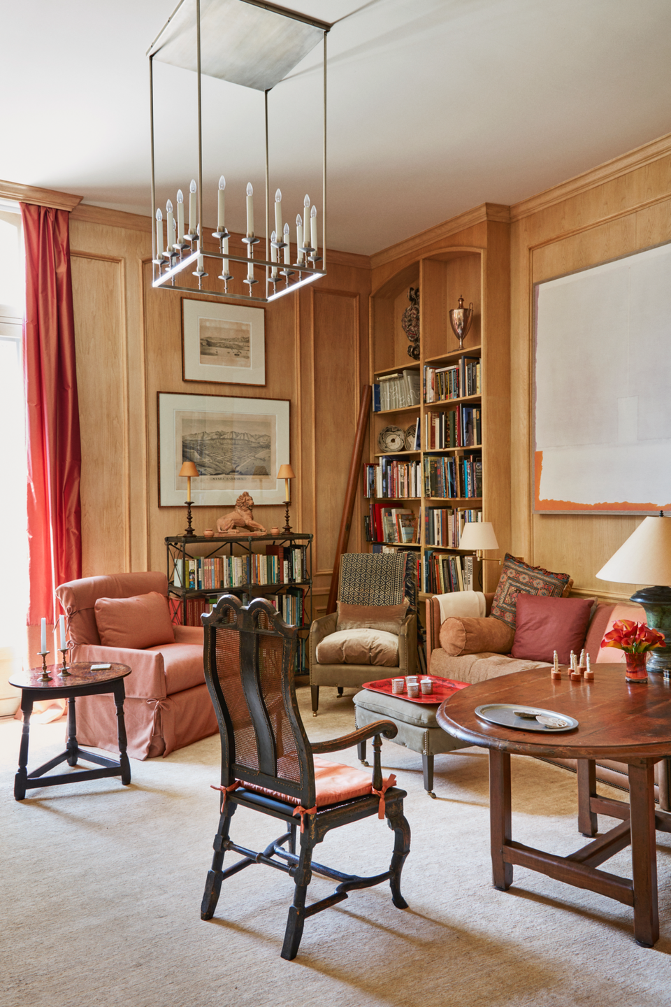 """<p>An eclectic mix of classicist and modernist styles, the Montecito getaway of <span>John Saladino</span> acts as urbane gallery of the designer's most treasured antiquities and art. A slick, modern <a href=""""http://www.remains.com/"""" rel=""""nofollow noopener"""" target=""""_blank"""" data-ylk=""""slk:Remains Lighting"""" class=""""link rapid-noclick-resp"""">Remains Lighting</a> chandelier offsets the rustic wall paneling of the library. The sofa from Saladino's own line features a <a href=""""https://www.dualoy.com/"""" rel=""""nofollow noopener"""" target=""""_blank"""" data-ylk=""""slk:Dualoy"""" class=""""link rapid-noclick-resp"""">Dualoy</a> leather and <a href=""""http://quadrillefabrics.com/"""" rel=""""nofollow noopener"""" target=""""_blank"""" data-ylk=""""slk:Quadrille"""" class=""""link rapid-noclick-resp"""">Quadrille</a> fabric. A <a href=""""http://fortuny.com/"""" rel=""""nofollow noopener"""" target=""""_blank"""" data-ylk=""""slk:Fortuny"""" class=""""link rapid-noclick-resp"""">Fortuny</a> cushion tops a Charles II-style caned armchair. The rug is from <a href=""""https://www.saccocarpet.com/"""" rel=""""nofollow noopener"""" target=""""_blank"""" data-ylk=""""slk:Sacco Carpet"""" class=""""link rapid-noclick-resp"""">Sacco Carpet</a>.</p>"""