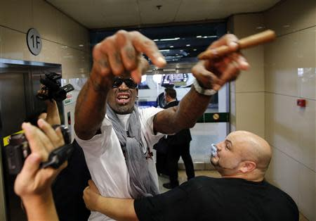 Former basketball star Dennis Rodman of the U.S. gestures as he talks to journalists chasing him upon his arrival at Beijing Capital International Airport September 7, 2013. REUTERS/Kim Kyung-Hoon