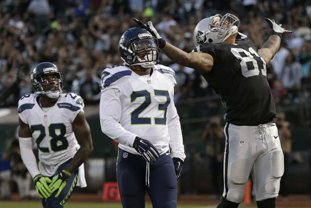 Oakland Raiders tight end Mychal Rivera (81) celebrates after catching a 20-yard touchdown in front of Seattle Seahawks cornerback Phillip Adams (28) and strong safety Jeron Johnson during (23) the first quarter of an NFL preseason football game in Oakland, Calif., Thursday, Aug. 28, 2014. (AP Photo/Marcio Jose Sanchez)