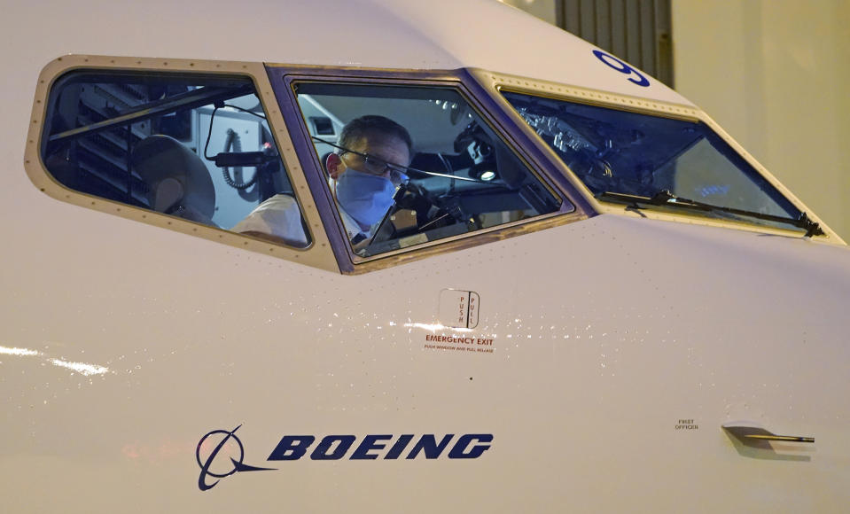 Capt. Brian Eyre, who was serving as first officer, goes through pre-flight preparations in the flight deck before the first Alaska Airlines passenger flight on a Boeing 737-9 Max airplane, Monday, March 1, 2021, prior to a flight to San Diego from Seattle-Tacoma International Airport in Seattle. The 737 Max, a mid-size plane used mostly on short and medium-range flights, recently returned to flying after being grounded worldwide for 20 months following two fatal crashes. Alaska plans to have four 737 Max airplanes in service by April. (AP Photo/Ted S. Warren)