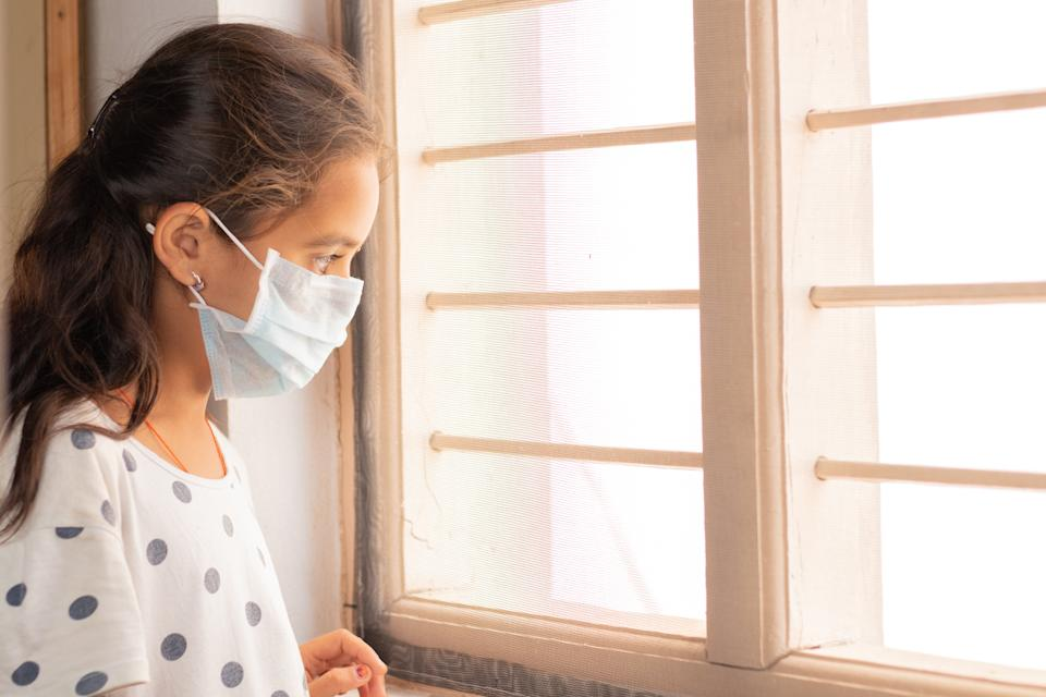 Sad young girl seeing through the window during home isolation watching out - Coronavirus or Covid-19 quarantine concept