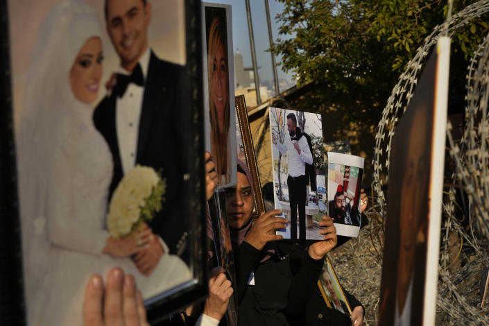 Relatives of victims of the Aug. 4, 2020, Beirut port explosion hold portraits of their loved ones during a protest near the Parliament building to demand an expedited investigation, in Beirut, Lebanon, Sunday, July 4, 2021. A year after the deadly blast, families of the victims are consumed with winning justice for their loved ones and punishing Lebanon's political elite, blamed for causing the disaster through their corruption and neglect. Critics say the political leadership has succeeded so far in stonewalling the judicial investigation into the explosion. (AP Photo/Hassan Ammar)