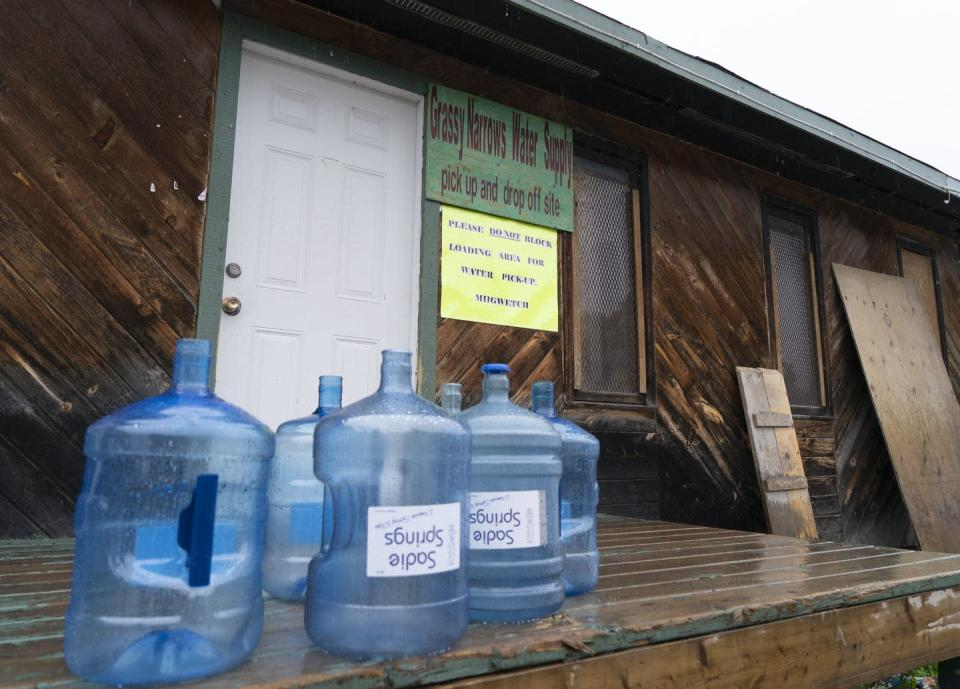 Water bottles sit on a porch, behind reads a sign that says 'Grassy Narrows Water Supply' with a smaller sign that reads 'please do not block loading area for water pickup'