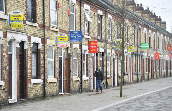 STOKE-ON-TRENT, ENGLAND - MARCH 03: A man walks past a street of terraced houses advertising properties To Let on March 03, 2021 in Stoke-on-Trent, England. UK Chancellor, Rishi Sunak, announced the return of 95% mortgages to help first-time buyers. He also announced that house buyers would be exempt from paying stamp duty for a further three months with the scheme ending on 31st June 2021. (Photo by Nathan Stirk/Getty Images)