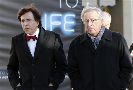 Luxembourg's outgoing PM Jean-Claude Juncker walks with Belgian PM Elio Di Rupo during an official visit to Luxembourg