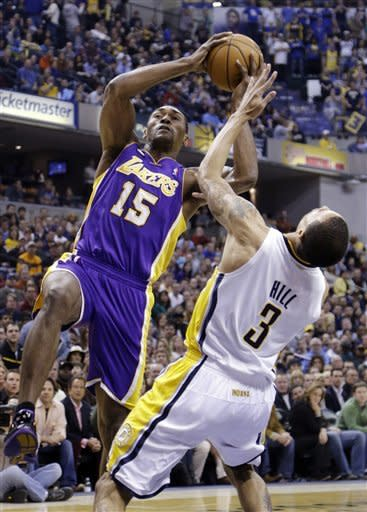 Indiana Pacers guard George Hill, right, takes the charge from Los Angeles Lakers forward Metta World Peace in the first half of an NBA basketball game in Indianapolis, Friday, March 15, 2013. (AP Photo/Michael Conroy)