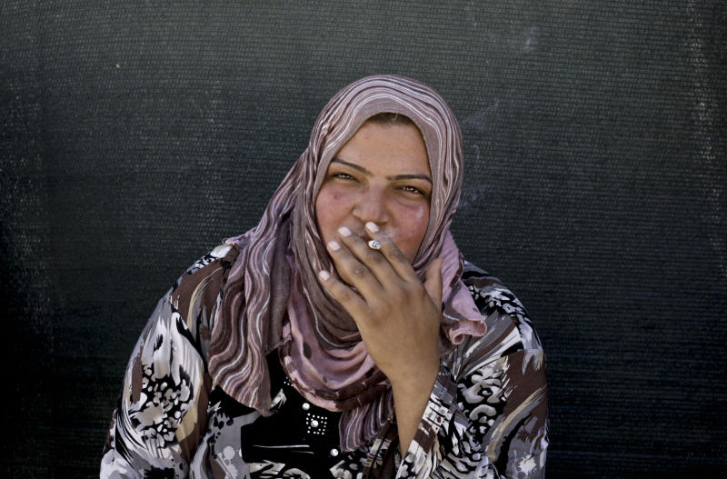 In this Wednesday, Sept. 11, 2013 photo, a Syrian refugee woman smokes a cigarette outside of her tent at a temporary refugee camp, in the eastern Lebanese town of al-Faour in the Bekaa valley, near the border with Syria. She is just one of Syria's refugees in Lebanon, driven out of their homes by a civil war that has killed more than 100,000 and displaced millions. (AP Photo/Nariman El-Mofty)