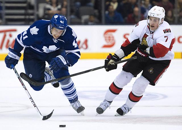 Toronto Maple Leafs forward Nikolai Kulemin, left, races for a loose puck against Ottawa Senators forward Kyle Turris, right, during the second period of an NHL preseason hockey game in Toronto on Tuesday, Sept. 24, 2013. (AP Photo/The Canadian Press, Nathan Denette)
