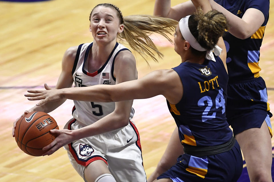 Connecticut's Paige Bueckers drives to the basket as Marquette's Selena Lott, right, defends, during the first half of an NCAA college basketball game in the Big East tournament finals at Mohegan Sun Arena, Monday, March 8, 2021, in Uncasville, Conn. (AP Photo/Jessica Hill)