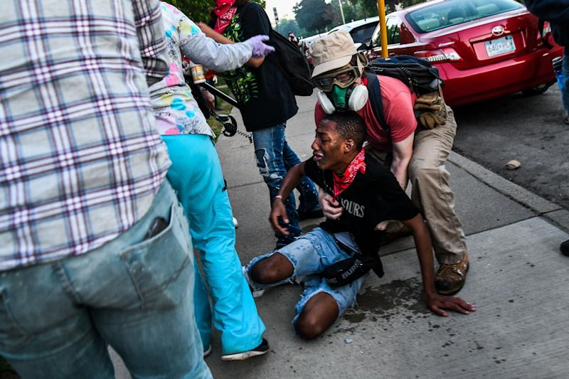 A protestor is assisted by medic protestors after being hit by tear gas near the 5th police precinct during a demonstration to call for justice for George Floyd, a Black man who died while in custody of the Minneapolis police, on May 30, 2020 in Minneapolis, Minnesota. (Photo by CHANDAN KHANNA/AFP via Getty Images) (Photo: CHANDAN KHANNA via Getty Images)